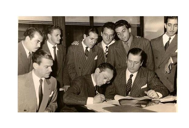 Mario Soto (Abajo izq.) observa como Pugliese (al centro) firma un contrato